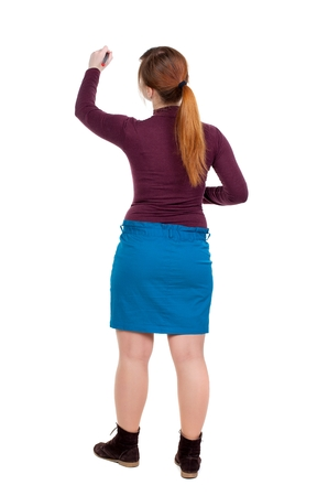 back view of writing beautiful woman. Girl with red hair tied in a pigtail draws felt-tip pen on the wall.