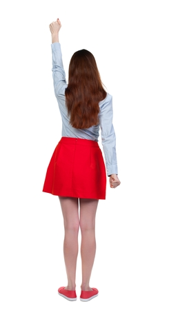 Back view of woman. Raised his fist up in victory sign. Long-haired brunette in red skirt held up his hand with his fists. Stock Photo