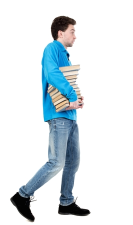 striding: side view of going man carries a stack of books. curly-haired student in a blue warm jacket carries books. side view.