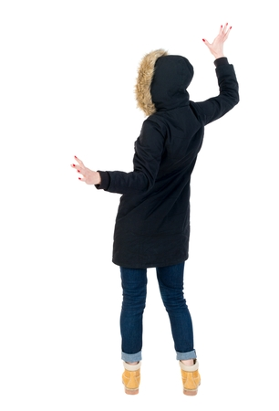 balances: Back view woman in winter jacket Balances waving his arms. Standing young girl in parka. Girl in warm winter black jacket waving his arms.