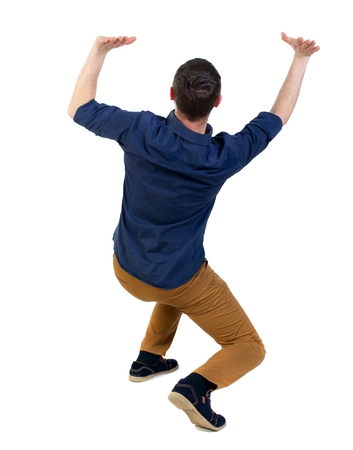 severity: back view of business man protects hands from what is falling from above. man in a blue shirt with the sleeves rolled up sitting down holding a severity on themselves.
