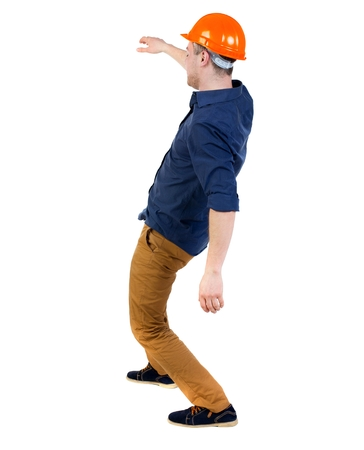 hombre cayendo: Balancing young man. or dodge the falling man. backside view of person. Isolated over white background. a man in a protective helmet falls