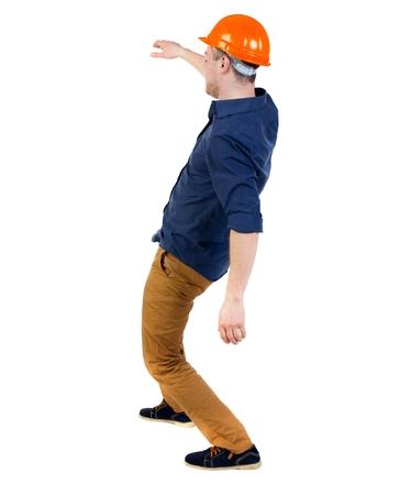 hombre cayendo: Equilibrio joven. o esquivar el hombre que cae. trasero vista de la persona. Aislado sobre fondo blanco. un hombre en un casco protector cae Foto de archivo