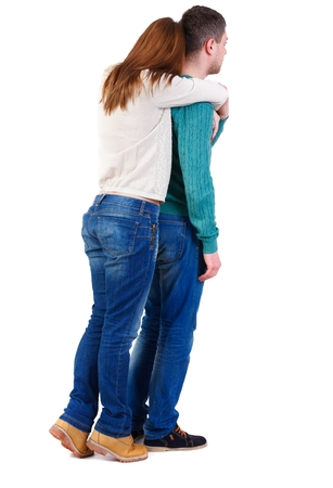 Back view of young embracing couple (man and woman) hug and look into the distance. girl in warm jacket standing on tiptoes hugging man from behind.
