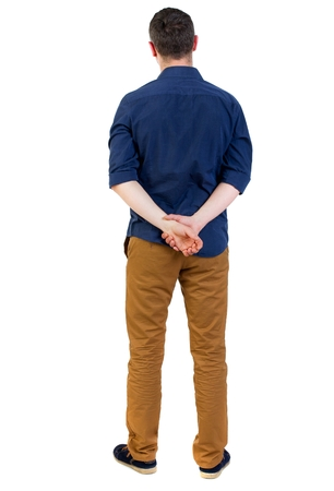 his shirt sleeves: Back view of man . Standing young guy. man in a blue shirt with the sleeves rolled up, standing with his hands behind his back.. Stock Photo