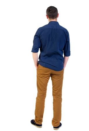 his shirt sleeves: Back view of man . Standing young guy. man in a blue shirt with the sleeves rolled up, standing with his hands in his pocket.