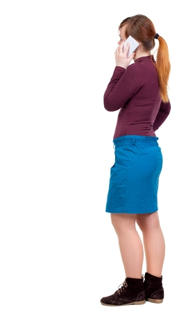 hair tied: back view of a woman talking on the phone. Girl with red hair tied in a ponytail is standing sideways and talking on a cell phone.