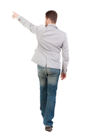 treading: Back view of going business man pointing. walking young guy . man in a gray jacket leaves the frame showing a finger in the side.