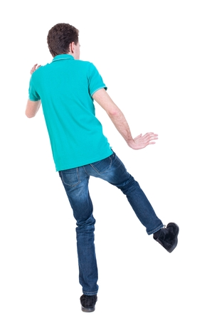 balances: back view of dancing young man. Curly man in a turquoise jacket balances on one leg.