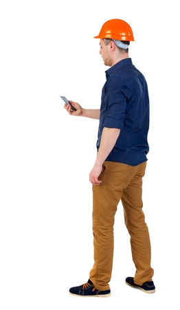 backview: Backview of business man in construction helmet stands and enjoys tablet or using a mobile phone. man in a blue shirt and helmet standing with phone in hand.