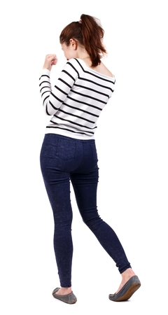 back view of woman funny fights waving his arms and legs. Girl in a striped sweater boxing. Standard-Bild
