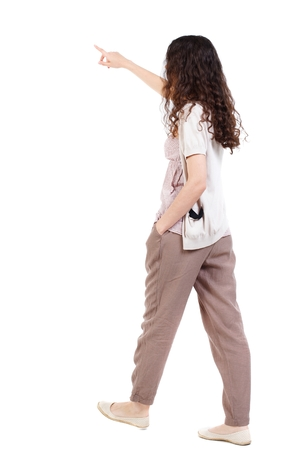 back view of pointing walking woman. going girl pointing. Long-haired curly girl is putting his hand in his pocket the other shows ahead.