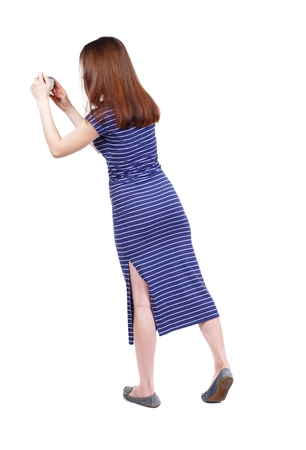 back view of standing young beautiful woman and using a mobile phone. brunette in a blue striped dress photographed on a compact camera standing on tiptoes.