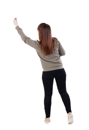 back view of writing beautiful woman. Isolated over white background. A young girl in a gray sweater pulled up with a felt-tip pen in a hand.