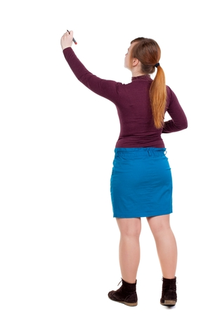 hair tied: back view of writing beautiful woman. Girl with red hair tied in a pigtail tip pen writes on the blackboard. Stock Photo