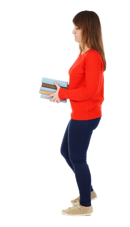 Girl comes with stack of books. side view. Girl in red sweater goes to the right with a stack of books. Stock Photo