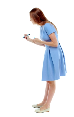 back view of writing beautiful woman. Isolated over white background. Skinny girl in a blue dress writes marker. side view