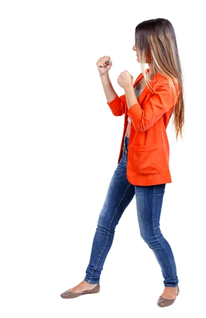 wimp: back view of woman funny fights waving his arms and legs. student in a red jacket in a boxing rack. Stock Photo