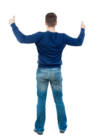 Back view of business man shows thumbs up. bearded man in blue pullover showing thumbs up with both hands. Stock Photo