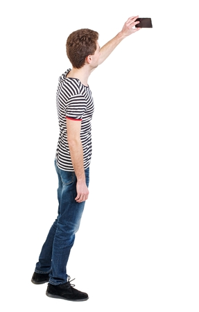 striped vest: back view of standing business man photographing a phone or tablet. Curly boy in a striped vest photographs on the phone that is at the top.