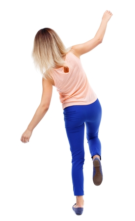 stumble: Balancing young woman. or dodge falling woman. Isolated over white background. The blonde in a pink t-shirt balancing on his leg. Stock Photo