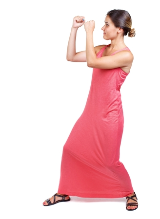wimp: skinny woman funny fights waving his arms and legs. slender woman in a long red dress in boxing pose. Stock Photo
