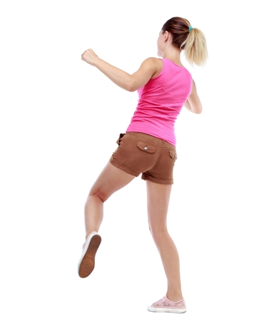 wimp: back view of woman funny fights waving his arms and legs. Isolated over white background. Sport blond in brown shorts hit someone