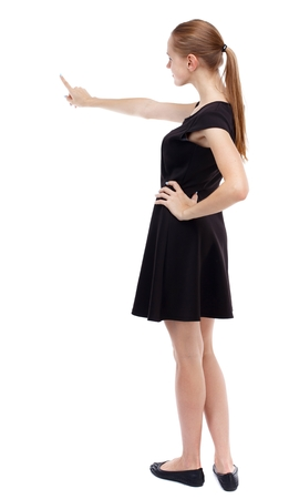 Back view of pointing woman. beautiful girl. Isolated over white background. Blonde in a short black dress pointing her finger.