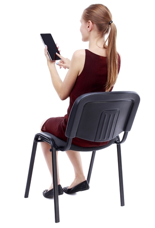 girl in burgundy dress: back view of woman sitting on chair and looks at the screen of the tablet. girl in a burgundy dress sitting on a chair and working with plashnetom.