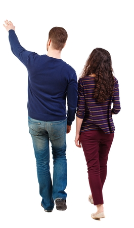 treading: Back view of walking young couple (man and woman) pointing. Rear view people collection. Swarthy girl and the bearded man on the move shows his hands up.