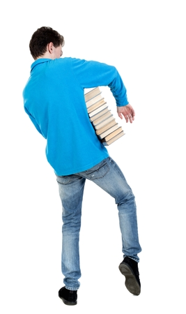 warm jacket: A man carries a heavy pile of books. back view. curly-haired student in a blue warm jacket came out of the library. Stock Photo