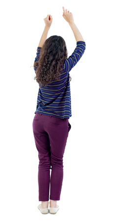 back view of dancing young beautiful woman. Long-haired curly girl in blue blouse dancing hands up. Stock Photo