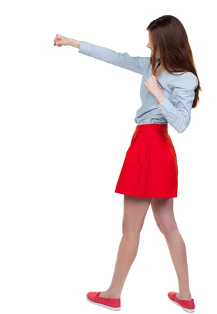 skinny woman funny fights waving his arms and legs. Long-haired brunette is cancer and has boxed in a red skirt Stock Photo