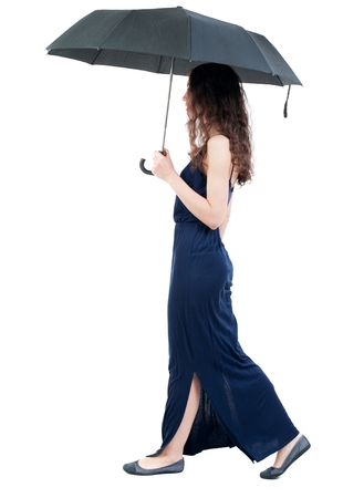 young woman in dress walking under an umbrella. dark curly girl in a blue evening dress is the rain. Stock Photo