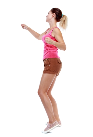 wimp: back view of woman funny fights waving his arms and legs. Isolated over white background. Sport blond in brown shorts boxing.