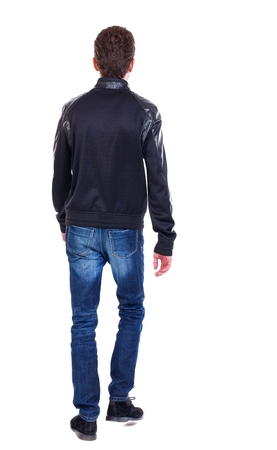 treading: Back view of going handsome man. walking young guy . Curly guy in a black leather jacket goes away. Stock Photo