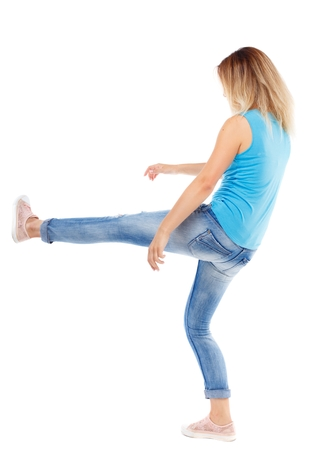 wimp: back view of woman funny fights waving his arms and legs. Isolated over white background. The blonde in a blue shirt and jeans, raised her leg. Stock Photo