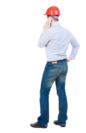 backview: Backview of business man in construction helmet stands and enjoys tablet or using a mobile phone. businessman in a white shirt and a construction helmet on the phone.