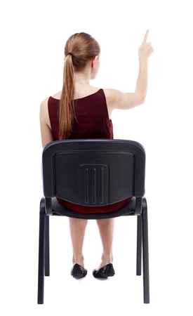 girl in burgundy dress: back view of young beautiful woman sitting on chair and pointing. girl in a burgundy dress sitting on a chair and presses his finger on the button. Stock Photo