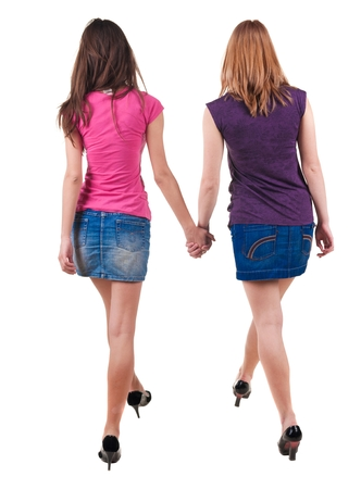 Back view of two young women walking brunette and blonde . Rear view people collection. backside view of person. beautiful woman friends walking. Rear view. Isolated over white background.