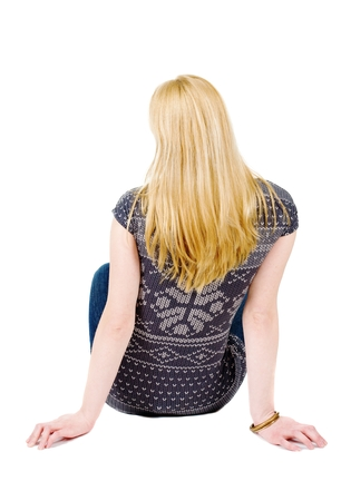 Back view of beautiful woman relaxes and looks into the distance. Blonde young girl sitting. Rear view people. Isolated over white background.