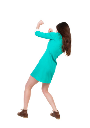 wimp: skinny woman funny fights waving his arms and legs. Isolated over white background. The girl in a dress beats foot in brown shoe. The girl in a green dress simply evade attacks. Stock Photo