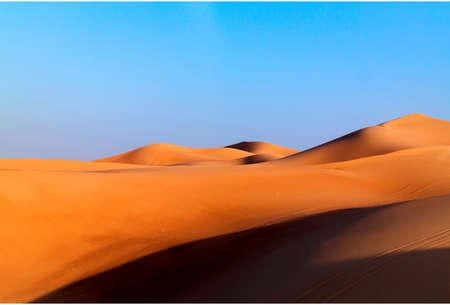 Arabian desert dune background on blue sky. Desert near the city of Dubai. large red and yellow dune illuminated by bright sunlight Stock Photo