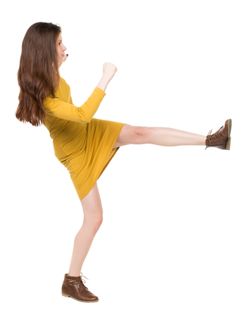 wimp: skinny woman funny fights waving his arms and legs. Isolated over white background. Girl engineer in the yellow dress standing right side and hit his left foot.