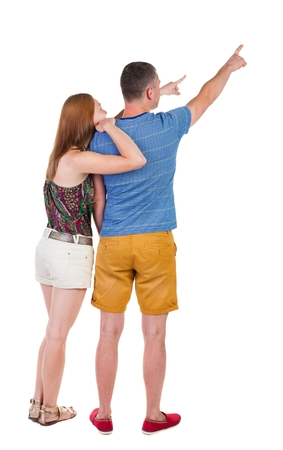 young couple in short pointing at wal Back view woman and man . Rear view people collection. backside view of person. Isolated over white background.