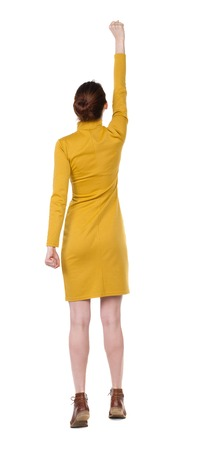 pal: Back view of  woman.  Raised his fist up in victory sign.  Rear view people collection.  backside view of person.  Isolated over white background. Girl in  dress standing in a pose superhero. Girl in mustard strict dress raised his right hand with the pal