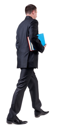 adult student: back view of walking  business man with books. going young guy in black suit. Isolated over white background. Rear view people collection. backside view of person Stock Photo