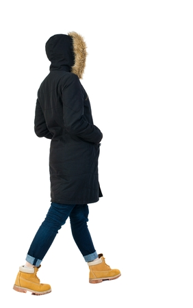 treading: Back view of going  woman in parka. walking young girl. Rear view people collection.  backside view of person.  Isolated over white background. The girl in a jacket goes with his hands in his pockets Stock Photo