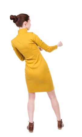 back view of standing woman pulling a rope from the top or cling to something.  Rear view people collection.  backside view of person.  Isolated over white background. Girl in a dress with a simple mustard hair tied in a bun pulling a rope to the right