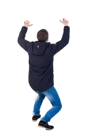 back view. man  in parka protects hands from what is falling from above. Man holding a heavy load Rear view people collection.  backside view of person.  Isolated over white background. The guy is on all fours and keeps the weight on yourself. A guy in a